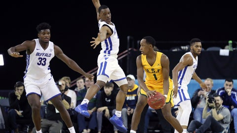 <p>               San Francisco's Jamaree Bouyea (1), centre right, drives to the basket against Buffalo's Davonta Jordan (4) and Nick Perkins (33), left, during the first half of an NCAA college basketball game between the Buffalo Bulls and the San Francisco Dons, in Belfast, Ireland, Saturday, Dec. 1, 2018, in Belfast. (AP Photo/Peter Morrison)             </p>