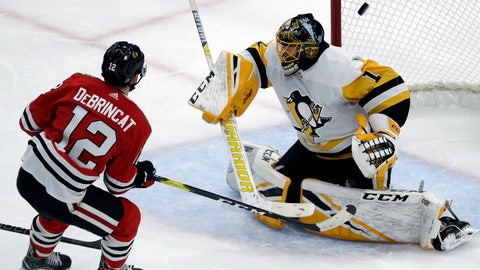 <p>               Chicago Blackhawks left wing Alex DeBrincat, left, scores against Pittsburgh Penguins goalie Casey DeSmith during the second period of an NHL hockey game Wednesday, Dec. 12, 2018, in Chicago. (AP Photo/Nam Y. Huh)             </p>