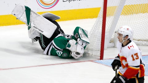 <p>               Dallas Stars goaltender Ben Bishop (30) lays on the ice after getting hit as Calgary Flames left wing Johnny Gaudreau (13) skates by during the second period of an NHL hockey game in Dallas, Tuesday, Dec. 18, 2018. (AP Photo/LM Otero)             </p>