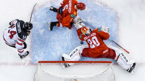 <p>               Russia goalie Pyotr Kochetkov (20) makes a save as Dmitri Samorukov (5) and Canada's Maxime Comtois (14) watch during the second period of a world junior hockey championships game in Vancouver, British Columbia, Monday, Dec. 31, 2018. (Darryl Dyck/The Canadian Press via AP)             </p>
