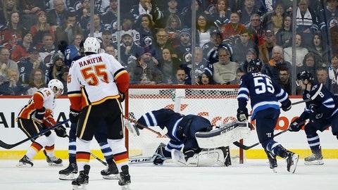 <p>               Winnipeg Jets Calgary Flames' Johnny Gaudreau (13) scores against Winnipeg Jets goaltender Connor Hellebuyck (37) during second-period NHL hockey game action in Winnipeg, Manitoba, Thursday, Dec. 27, 2018. (John Woods/The Canadian Press via AP)             </p>