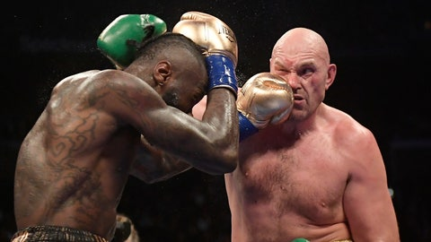 Deontay Wilder left connects with Tyson Fury of England during a WBC heavyweight championship boxing match Saturday Dec. 1 2018 in Los Angeles