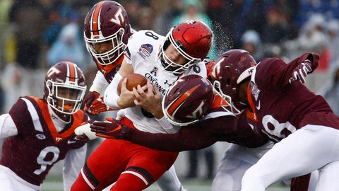 <p>               Cincinnati quarterback Hayden Moore, center, is tackled by a group of Virginia Tech defenders as he rushes the ball in the first half of the Military Bowl NCAA college football game, Monday, Dec. 31, 2018, in Annapolis, Md. (AP Photo/Patrick Semansky)             </p>