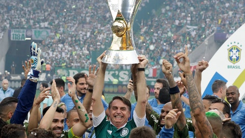 <p>               Brazil's President-elect Jair Bolsonaro holds up the Brazilian soccer championship trophy, as he celebrates with Palmeiras soccer club who won the title after defeating Vitoria, in Sao Paulo, Brazil, Sunday, Dec. 2, 2018. (AP Photo/Andre Penner)             </p>