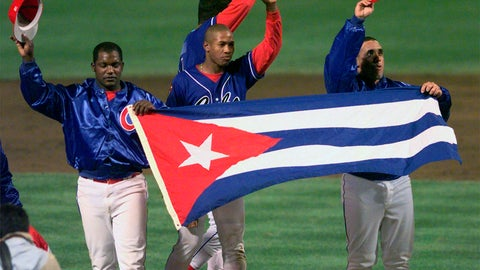 <p>               FILE - In this Monday, May 3, 1999 file photo, members of the Cuban baseball team carry their country's flag onto the field after a baseball game against the Baltimore Orioles at Camden Yards in Baltimore. Major League Baseball, its players' association and the Cuban Baseball Federation reached an agreement that will allow players from the island nation to sign big league contracts without defecting, an effort to eliminate the dangerous trafficking that had gone on for decades. The agreement runs through Oct. 31, 2021. (AP Photo/Nick Wass, File)             </p>