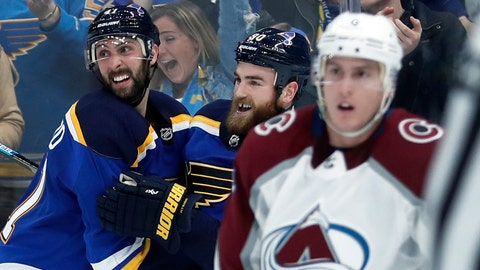 St. Louis Blues' Ryan O'Reilly, center, is congratulated by Robert Bortuzzo, left, as Colorado Avalanche's Tyson Barrie, right, skates past after O'Reilly scored the game-winning goal during overtime of an NHL hockey game Friday, Dec. 14, 2018, in St. Louis. The Blues won 4-3 in overtime. (AP Photo/Jeff Roberson)