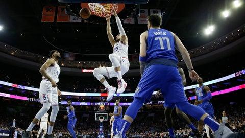 <p>               Philadelphia 76ers' Ben Simmons (25) hangs on the rim after a dunk as Jonah Bolden (43) and Dallas Mavericks' Luka Doncic (77) look on during the first half of an NBA basketball game, Saturday, Jan. 5, 2019, in Philadelphia. (AP Photo/Matt Slocum)             </p>
