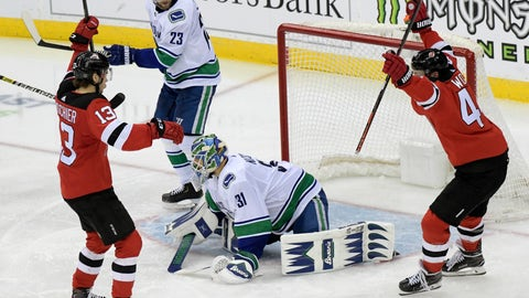 <p>               New Jersey Devils' Nico Hischier (13) and Miles Wood (44) celebrate a goal by Sami Vatanen, not pictured, as Vancouver Canucks goaltender Anders Nilsson (31) and Alexander Edler (23) react during the third period of an NHL hockey game Monday, Dec. 31, 2018, in Newark, N.J. The Devils defeated the Canucks 4-0. (AP Photo/Bill Kostroun)             </p>