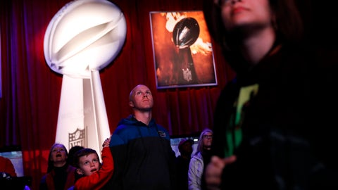 <p>               Kyle Williams, right, and his son Grant, 8, of Monroe, Ga., watch a video while waiting in line to see the Vince Lombardi Trophy at the NFL Experience ahead of Sunday's Super Bowl 53 football game between the Los Angeles Rams and New England Patriots in Atlanta, Wednesday, Jan. 30, 2019. (AP Photo/David Goldman)             </p>