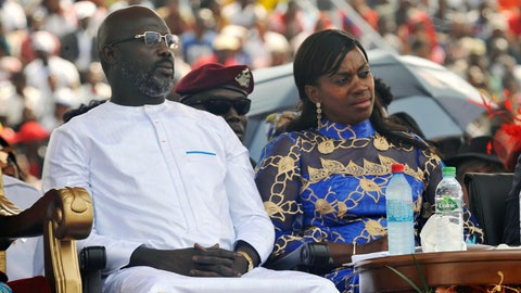 """<p>               FILE - In this Jan. 22, 2018, file photo, Liberia's new President George Weah, left and his wife, Clar Weah, right, sit during his inauguration ceremony in Monrovia Liberia. Star footballer-turned-politician George Weah marks a year as Liberia's president on Tuesday Jan. 22, 2019, as many in the impoverished country debate whether he has begun to deliver on dramatic campaign promises. FIFA's 1995 player of the year in his inaugural speech vowed to give the West African nation's young population hope through job creation and a war on corruption, saying """"Liberians will no longer be spectators in their own economy."""" (AP Photo/Abbas Dulleh, File)             </p>"""