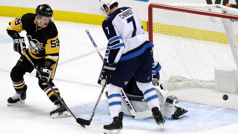 <p>               Pittsburgh Penguins' Jake Guentzel (59) watches as a shot from the point by Olli Maatta (3) gets past Winnipeg Jets goaltender Connor Hellebuyck, rear, and Ben Chiarot (7) during the first period of an NHL hockey game in Pittsburgh, Friday, Jan. 4, 2019. (AP Photo/Gene J. Puskar)             </p>
