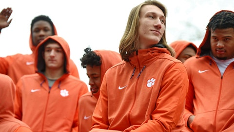 """<p>               FILE - In this Saturday, Jan. 12, 2019, file photo, Clemson quarterback Trevor Lawrence, foreground, and fellow freshmen ride in the parade honoring the football team, in Clemson, S.C., after the Tigers defeated Alabama 44-16 in the NCAA College Football Playoff championship game several days earlier. Lawrence was falsely quoted criticizing """"coastal elite media"""" after the Clemson football team's White House visit on Monday, Jan. 14. (AP Photo/Richard Shiro, File)             </p>"""