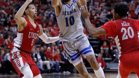 <p>               Nevada's Caleb Martin drives between UNLV's Noah Robotham, left, and Nick Blair during the second half of an NCAA college basketball game Tuesday, Jan. 29, 2019, in Las Vegas. Nevada won 87-70. (AP Photo/John Locher)             </p>