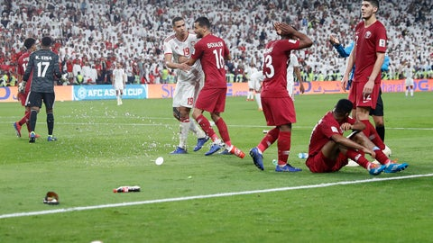 <p>               Qatar's defender Salem Al Hajri, right bottom, lies on the pitch after shoes and bottles where thrown in by United Arab Emirates fans during the AFC Asian Cup semifinal soccer match between United Arab Emirates and Qatar at Mohammed Bin Zayed Stadium in Abu Dhabi, United Arab Emirates, Tuesday, Jan. 29, 2019. (AP Photo/Hassan Ammar)             </p>