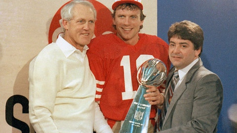 <p>               FILE - In this Jan. 20, 1985, file photo, San Francisco 49ers quarterback Joe Montana, center, holds the Lombardi Trophy with coach Bill Walsh, left, and 49ers owner Edward DeBartolo, Jr., in Stanford, Calif. There is no denying the impact on the coaching world that Walsh and Bill Parcells have had. The hard evidence is apparent again as the NFL playoffs begin. All 12 of the coaches have some sort of tie-in to either three-time Super Bowl champion Walsh or two-time winner Parcells. Yes, all 12. (AP Photo, File)             </p>
