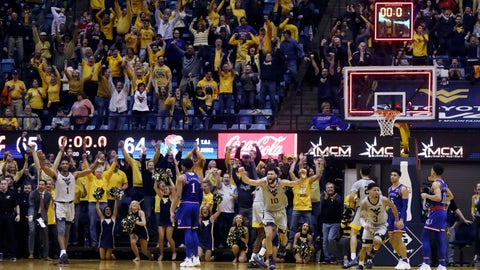 West Virginia players celebrates their 65-64 win over No 7 Kansas in an NCAA college basketball game, Saturday, Jan. 19, 2019, in Morgantown, W.Va. (AP Photo/Raymond Thompson)