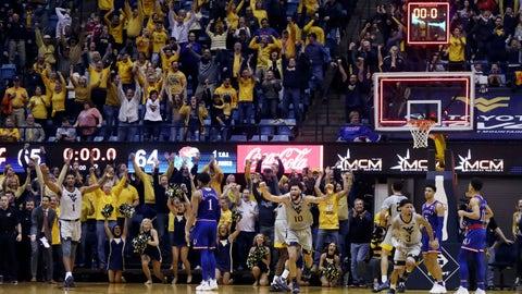 West Virginia players celebrates their 65-64 win over No 7 Kansas in an NCAA college basketball game, Saturday, Jan. 19, 2019, in Morgantown, W.Va. (AP Photo/Raymond Thompson)