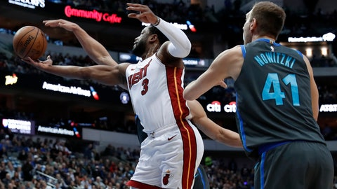 <p>               Miami Heat guard Dwyane Wade (3) shoots as Dallas Mavericks' Dirk Nowitzki (41) and Dwight Powell, rear, defend during the first half of an NBA basketball game in Dallas, Wednesday, Feb. 13, 2019. (AP Photo/Tony Gutierrez)             </p>