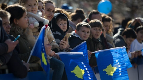 """<p>               Kosovars wave national flags as they wait to watch a military parade, during celebrations to mark the 11th anniversary of independence in Pristina, Sunday, Feb. 17, 2019. Thousands of civilians filled downtown Pristina Sunday decorated with national and U.S. flags while infantry troops with light weaponry of the Kosovo Security Forces, now transformed into a regular army, paraded as a """"professional, multiethnic army serving the youngest country in the world,"""" as President Hashim Thaci said.  (AP Photo/Visar Kryeziu)             </p>"""
