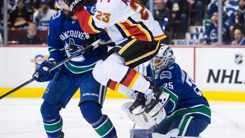 <p>               Calgary Flames' Sean Monahan (23) jumps in front of Vancouver Canucks goalie Jacob Markstrom, of Sweden, as he makes a glove save while Erik Gudbranson, back left, defends during the first period of an NHL hockey game Saturday, Feb. 9, 2019, in Vancouver, British Columbia. (Darryl Dyck/The Canadian Press via AP)             </p>