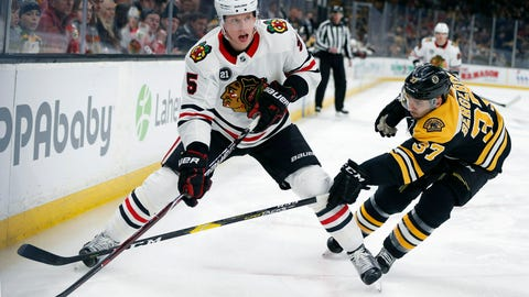 <p>               Boston Bruins' Patrice Bergeron (37) battles Chicago Blackhawks' Connor Murphy (5) for the puck during the first period of an NHL hockey game in Boston, Tuesday, Feb. 12, 2019. (AP Photo/Michael Dwyer)             </p>