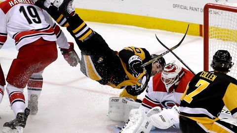 <p>               Pittsburgh Penguins' Garrett Wilson, center, is upended next to Carolina Hurricanes goaltender Curtis McElhinney, second from right, during the first period of an NHL hockey game in Pittsburgh, Tuesday, Feb. 5, 2019. (AP Photo/Gene J. Puskar)             </p>