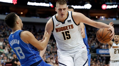 <p>               Dallas Mavericks guard Jalen Brunson (13) is knocked backward while defending against a drive to the basket by Denver Nuggets center Nikola Jokic (15) during the first half of an NBA basketball game in Dallas, Friday, Feb. 22, 2019. Jokic was called for charging on the play. (AP Photo/Tony Gutierrez)             </p>