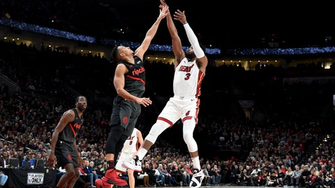 <p>               Miami Heat guard Dwyane Wade, right, hits a shot over Portland Trail Blazers guard CJ McCollum, center, as forward Al-Farouq Aminu watches during the first half of an NBA basketball game in Portland, Ore., Tuesday, Feb. 5, 2019. (AP Photo/Steve Dykes)             </p>