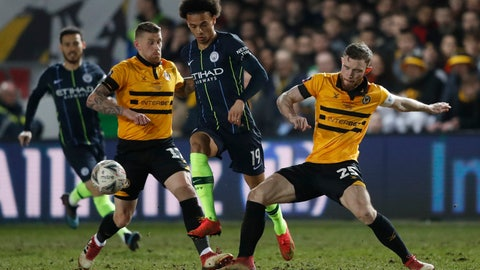 <p>               Manchester City's Leroy Sane, center, runs with the ball between Newport County's Mark O'Brien, right, and Newport County's Scot Bennett during the English FA Cup fifth round soccer match between Newport County and Manchester City at Rodney Parade stadium in Newport, Wales, Saturday, Feb. 16, 2019. (AP Photo/Frank Augstein)             </p>