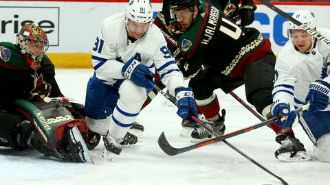<p>               Toronto Maple Leafs center John Tavares (91) and left wing Zach Hyman (11) battle with Arizona Coyotes defenseman Niklas Hjalmarsson (4) for the puck as Coyotes goaltender Darcy Kuemper, left, watches the puck during the first period of an NHL hockey game Saturday, Feb. 16, 2019, in Glendale, Ariz. (AP Photo/Ross D. Franklin)             </p>