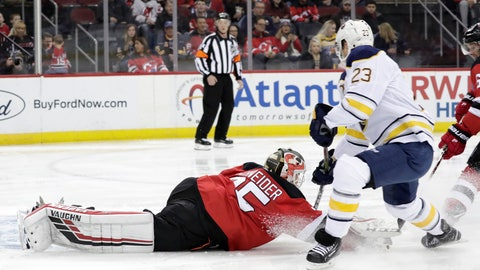 <p>               New Jersey Devils goaltender Cory Schneider (35) dives forward to deflect the puck as Buffalo Sabres center Sam Reinhart (23) attacks during the first period of an NHL hockey game, Sunday, Feb. 17, 2019, in Newark, N.J. (AP Photo/Julio Cortez)             </p>
