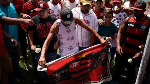 <p>               A fan holds a Flamengo flag as he and other fans pay a homage to the fire victims at the entrance Flamengo soccer club training complex in Rio de Janeiro, Brazil, Friday, Feb. 8, 2019. A fire tore through the sleeping quarters of the Flamengo soccer club development league, one of Brazil's most popular professional soccer clubs, killing several people who were most likely players and injuring others, authorities said. (AP Photo/Leo Correa)             </p>