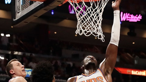 <p>               Phoenix Suns center Deandre Ayton (22) shoots and scores against Miami Heat forward Duncan Robinson (55) and Miami Heat center Hassan Whiteside (21) during the first half of an NBA basketball game Monday, Feb. 25, 2019, in Miami. (AP Photo/Brynn Anderson)             </p>