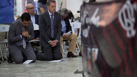 <p>               Flamengo soccer club president Rodolfo Landim, right, attends a mass in honor of the 10 teenage soccer players who were killed by a fire at the Flamengo training center last Friday, in Rio de Janeiro, Brazil, Friday, Feb. 15, 2019. The victims were between 14 and 16 years old. Police are still investigating what caused the fire. (AP Photo/Silvia Izquierdo)             </p>