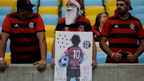 <p>               A man holds a drawing of a teenager in a Flamengo kit, as he waits for the start of a homage for the 10 teenage players killed by a fire at the Flamengo training center last Friday, at the Maracana Stadium, in Rio de Janeiro, Brazil, Thursday, Feb. 14, 2019, ahead of a soccer match between Flamengo and Fluminense. (AP Photo/Leo Correa)             </p>