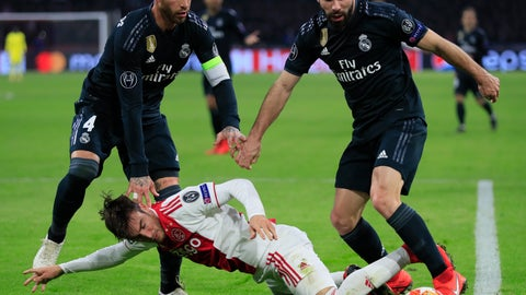 <p>               Ajax's Nicolas Tagliafico, center, is tackled by Real defender Dani Carvajal, right, and Real defender Sergio Ramos during the first leg, round of sixteen, Champions League soccer match between Ajax and Real Madrid at the Johan Cruyff ArenA in Amsterdam, Netherlands, Wednesday Feb. 13, 2019. (AP Photo/Peter Dejong)             </p>
