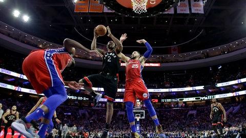 <p>               Toronto Raptors' Kawhi Leonard, center, goes up for a shot between Philadelphia 76ers' Ben Simmons, right, and Joel Embiid during the second half of an NBA basketball game, Tuesday, Feb. 5, 2019, in Philadelphia. Toronto won 119-107. (AP Photo/Matt Slocum)             </p>