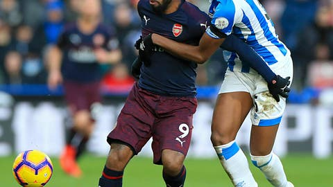 <p>               Arsenal's Alexandre Lacazette, left, and Huddersfield Town's Terence Kongolo battle for the ball during the English Premier League soccer match at the John Smith's Stadium in Huddersfield, England, Saturday Feb. 9, 2019. (Mike Egerton/PA via AP)             </p>