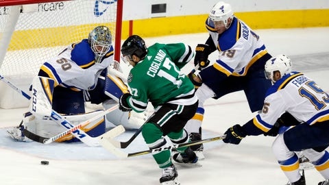 St. Louis Blues goaltender Jordan Binnington (50) gets help from defenseman Jay Bouwmeester (19) and center Robby Fabbri (15) as Dallas Stars center Andrew Cogliano (17) works to take a shot during the first period of an NHL hockey game in Dallas, Thursday, Feb. 21, 2019. (AP Photo/Tony Gutierrez)