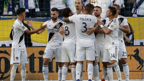 <p>               Los Angeles Galaxy forward Zlatan Ibrahimovic, center, is hugged by teammates after scoring against the Portland Timbers during the first half of an MLS soccer match Sunday, March 31, 2019, in Carson, Calif. (AP Photo/Marcio Jose Sanchez)             </p>