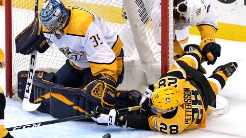 <p>               Pittsburgh Penguins' Marcus Pettersson (28) tries to get his stock on a rebound in front of Nashville Predators goaltender Pekka Rinne (35) after colliding with Filip Forsberg, rear, during the first period of an NHL hockey game in Pittsburgh, Friday, March 29, 2019. (AP Photo/Gene J. Puskar)             </p>