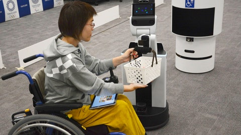 <p>               A robot passes a basket containing drinks to a woman in wheelchair during an unveiling event in Tokyo Friday, March 15, 2019. Organizers on Friday showed off robots that will be used at the new National Stadium to provide assistance for fans using wheelchairs. (Kyodo News via AP)             </p>