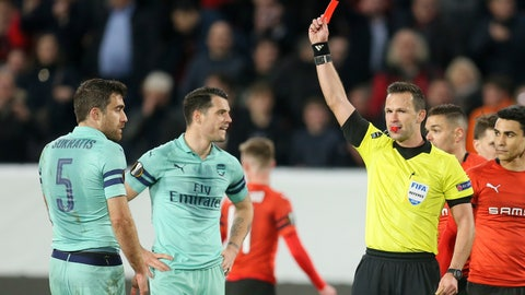 <p>               Ivan Kruzliak of Slovakia shows the red card to Arsenal's Sokratis Papastathopoulos, left, during the Europa League round of 16, first leg soccer match between Rennes and Arsenal at Roazhon Park in Rennes, northwestern France, Thursday, March 7, 2019. (AP Photo/David Vincent)             </p>