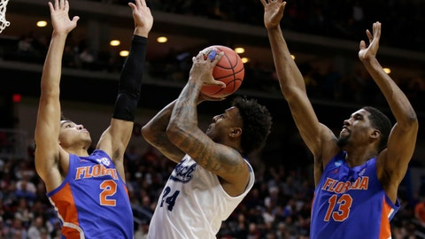 <p>               Nevada's Jordan Caroline (24) shoots between Florida's Andrew Nembhard (2) and Kevarrius Hayes (13) during the first half of a first round men's college basketball game in the NCAA Tournament in Des Moines, Iowa, Thursday, March 21, 2019. (AP Photo/Nati Harnik)             </p>