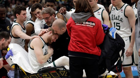 <p>               Michigan State players gather as Kyle Ahrens (0) is taken off the court after getting injured during the first half of an NCAA college basketball championship game against Michigan in the Big Ten Conference tournament, Sunday, March 17, 2019, in Chicago. (AP Photo/Nam Y. Huh)             </p>