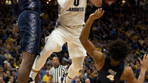 <p>               Marquette guard Markus Howard, center, drives to the basket against Georgetown forward Josh LeBlanc, left, and guard Jagan Mosely, right, during the first half of an NCAA college basketball game Saturday, March 9, 2019, in Milwaukee. (AP Photo/Darren Hauck)             </p>