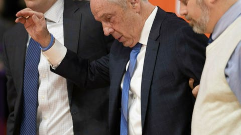 <p>               North Carolina coach Roy Williams is escorted off the court and waves, after falling near the bench during the first half of the team's NCAA college basketball game against Clemson on Saturday, March 2, 2019, in Clemson, S.C. (Robert Willett/The News & Observer via AP)             </p>