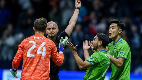<p>               Referee Robert Sibiga shows a yellow card to Seattle Sounders' Kim Kee-hee, right, near Sounders' Stefan Frei (24) and Cristian Roldan, middle, during the second half of the team's MLS soccer match against the Vancouver Whitecaps on Saturday, March 30, 2019, in Vancouver, British Columbia. (Ben Nelms/The Canadian Press via AP)             </p>