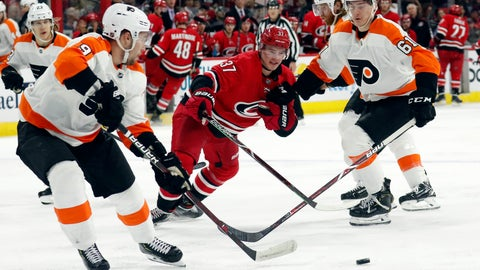 <p>               Philadelphia Flyers' Ivan Provorov (9) of Russia and Philippe Myers (61) battle Carolina Hurricanes' Andrei Svechnikov (37) of Russia for the puck during the third period of an NHL hockey game in Raleigh, N.C. on Saturday, March 30, 2019. (AP Photo/Chris Seward)             </p>