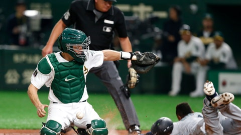 <p>               Oakland Athletics catcher Nick Hundley, left, cannot catch a throw as Seattle Mariners' Tim Beckham scores on in the third inning of Game 1 of their Major League opening baseball series at Tokyo Dome in Tokyo, Wednesday, March 20, 2019. (AP Photo/Toru Takahashi)             </p>